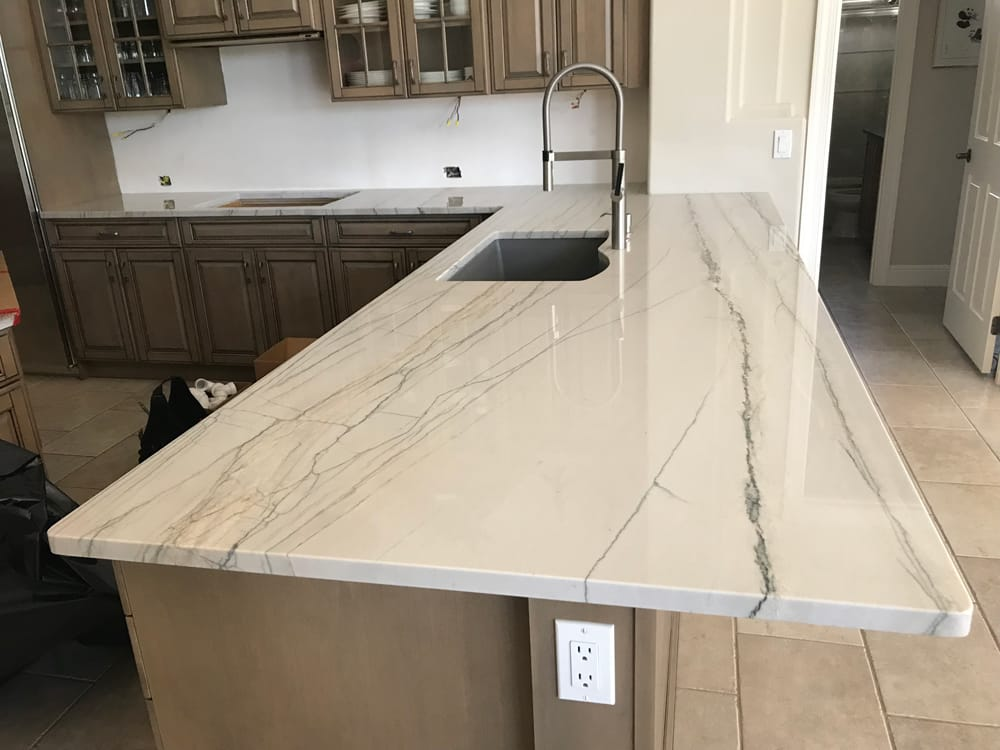 White quartz countertop with a sink in the middle and brown cabinets
