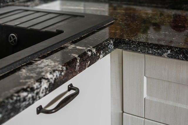 Darker tone granite countertop with white cabinets