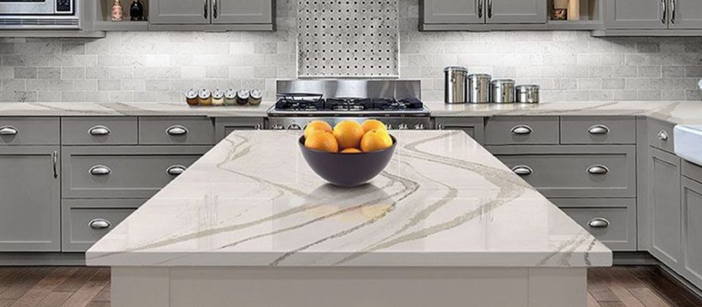 Modern kitchen in the background, clean white quartz countertop centered with a bowl of oranges on its top.